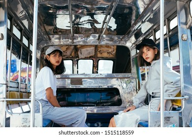 Thai girls sitting in baht bus, looking to the camera at back side of baht bus.