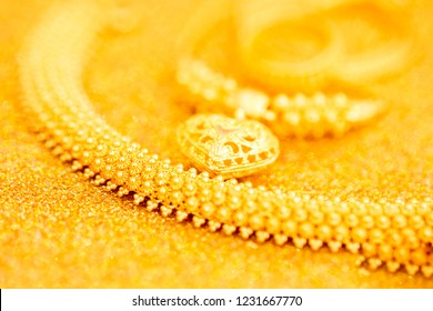 Thai gold jewelry series : set of Thai vintage pattern design gold ornament on shiny shimmering gold table space ( 96.5% gold karat )