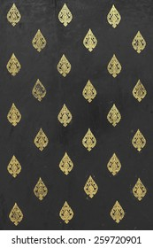 Thai golden leaves pattern on black grungy wood