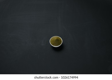 Thai green curry paste in a small bowl isolated on blackboard background.