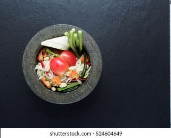 Thai green papaya salad (Som tum) in granite mortar on dark background