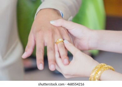 Thai groom wearing wedding ring for his bride , blur background
