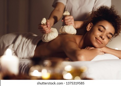 Thai herb compress massage. Woman relaxing in beauty spa, lying with closed eyes
