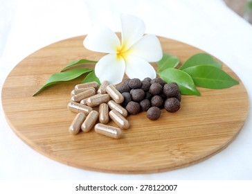 Thai herbal medicine, medicine ball lyrics Supplements in wooden tray decorated with white flower and green leaves with a white cotton background