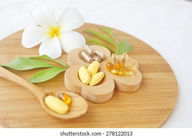 Thai herbal medicine, vitamins and Supplements in wooden tray and spoon decorated with white flower and green leaves with a white cotton background
