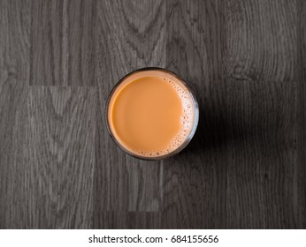 Thai hot milk tea on black wooden table background in top view