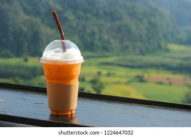 Thai iced tea in plastic cup with natual view as background.