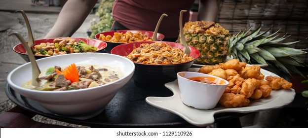 A Thai inspired food spread, including pineapple fried rice, green beef curry, Thai pepper chicken, and sweet and sour chicken.