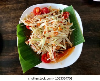 Thai Isan food, spicy papaya salad on the banana leaf decorated white plate on the dark wooden table background