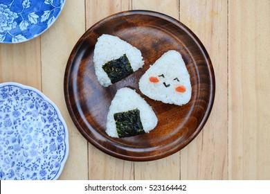 Thai jasmine rice ball (onigiri,musubi) on ceramic plate wooden table, selective focus