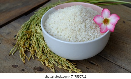 Thai jasmine rice in ceramic bowl placed on wooden background.
