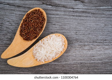 Thai Jasmine white and red rice in wooden spoons on wooden background
