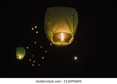 Thai lanterns thrown into the air at night