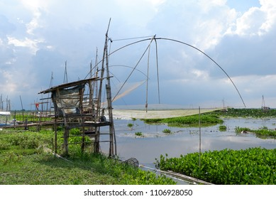 Thai local fishing equipment, made by wood and net,riverbank way of life,river side people life style,traditional,livelihood,rim river scenery at noon before rain,overcast,feel in wide nature,outdoor