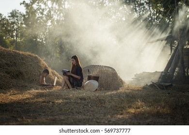 Thai local woman listening radio and her brother playing computer notebook beside a pile of straw in countryside Thailand