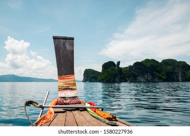 Thai long tail boat in Phang Nga Bay, Thailand. Karst rock formations in the distance