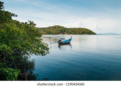 Thai Longtail Fishing Boat at Koh Tean mangrove forest near Samui island in summer day with blue sky, Thailand tropical island