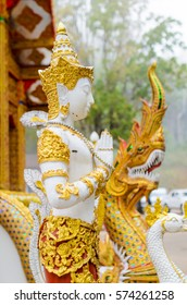 Thai male angle traditional style sculpture standing in front of a temple