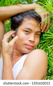 A Thai man in white tank top pose sissy in the garden