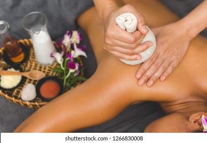 Thai Massage of  asian woman in spa room. Beautiful young woman having massage with herbal compress balls in therapy spa salon.