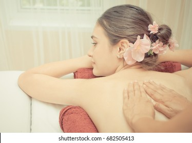 Thai Massage Therapist is rubbing oil on a woman's back
