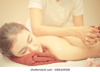 Thai massage using elbow to massage a woman back