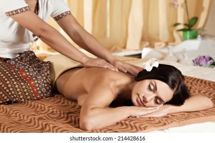 Thai massagist doing massage for european woman in spa salon