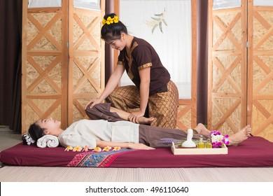 Thai massagist doing massage for woman in spa salon