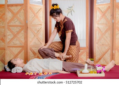 Thai Masseuse doing massage for woman in spa salon. Asian beautiful woman getting thai herbal massage compress massage in spa.She is very relaxed.  Beauty thai Massage concept.