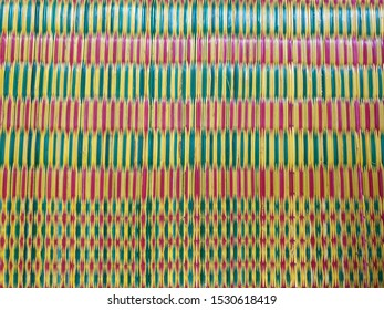 Thai mat woven from plastic in red green and yellow color (Thai native weave mat)