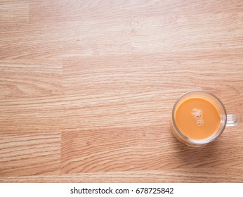 Thai milk tea on bottom right of wooden table background in top view with copy space