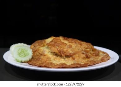 Thai Minced Pork Omelet on Rice - Kao Kai Jeaw Moo Sap - Thai cheapest delicious famous comfort food /street food, on black background.