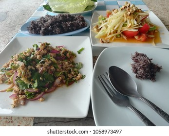 Thai minced pork salad served with  papaya salad and black sticky rice.