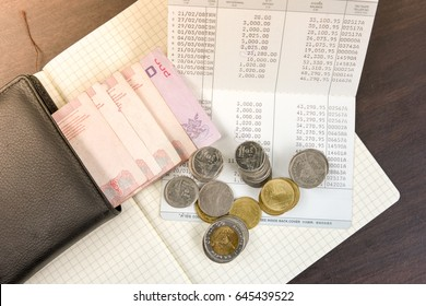 Thai money and bank saving account book on wooden table, money savings concept