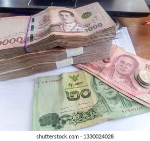 Thai money banknotes 1000 baht, 100 baht, 20 baht and 1 baht placed on the wooden floor, business investment concept.