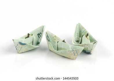 Thai money folded into the shape of a boat. On a white background.