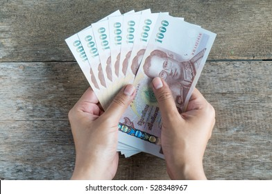 Thai money in hand for saving on wood background