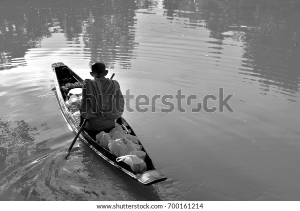 A Thai monk is using a boat to seek alms