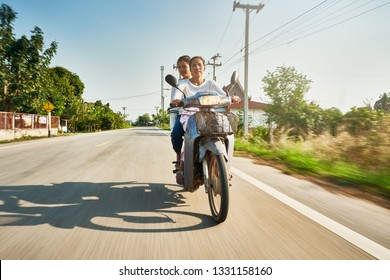 thai mother and daughter riding motorbike through rural thailand