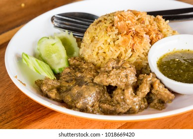 """Thai Muslim local traditional yellow boiled rice with dry sliced beef meat, """"Khao Mok Nuea"""", with crispy fried sliced shallot and sweet sauce, with shadow, close up"""