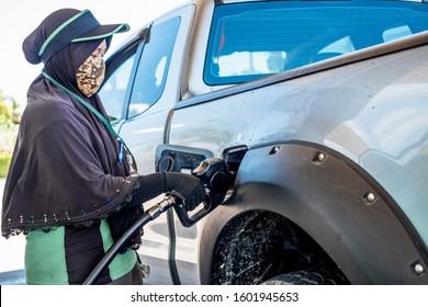 Thai muslim woman worker wearing hijab filling fuel for a car with petrol gun at gas station.