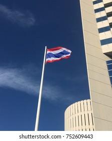 Thai National flag against blue sky beside building