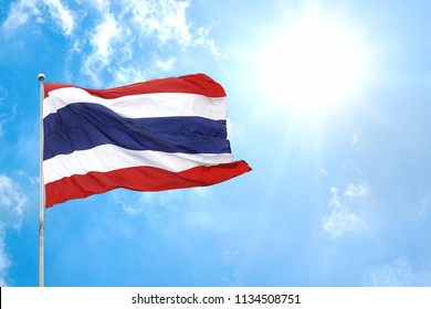 Thai national flag of Thailand waving blown and ripple away by wind with beautiful blue sky,clouds and sun in background.Copy space empty blank.