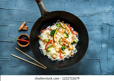 thai noodle in wok with fried vegetables on gray concrete background. top view flat lay with copy space