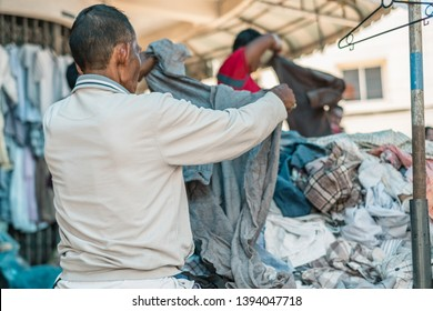 Thai old senior man choosing second hand cloth on street. Thai people lifestyle.