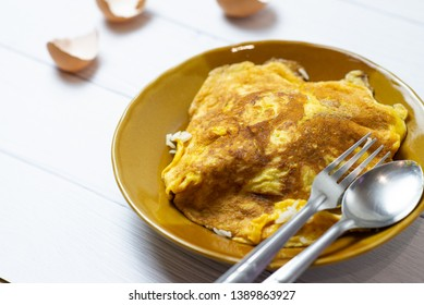 Thai Omelette or fried egg little scorched on brown ceramic dish with spoon. beside egg shell on white table. Thai street food. Traditional Thai style food. Homemade food.Simply food.