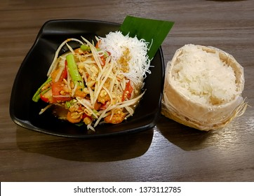 Thai papaya salad with hot sticky rice. on Table wood light brown color, top view ,Som Tum from Thailand