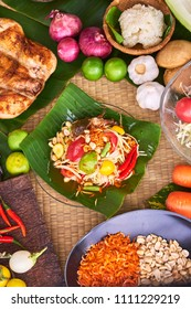 Thai papaya salad , Somtam (Street food), with roasted chicken and fresh crab  in banana leaf dish on traditional mat  decorating with many ingredients such garlic, shallot, papaya, tomato, cow pea,