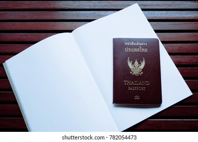 Thai Passport is on blank pages of notebook and they are on wooden table, tourism concept