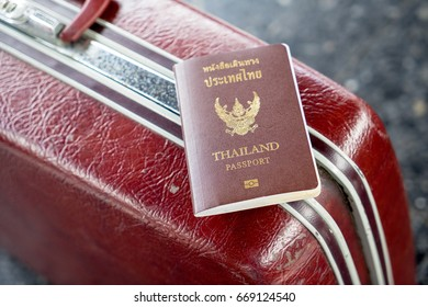 Thai passport on red vintage luggage